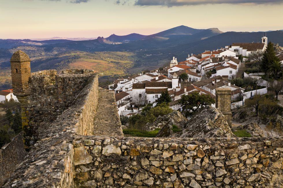 Sua muralha escarpada do século XIII rodeia a aldeia de casas brancas. A quase 900 metros de altitude, essa vila medieval olha para a Espanha, com sua igreja do século XV e sua casa do Governador de antanho, hoje transformada em banco, embora mantenha sua varanda de ferraria do século XVII.