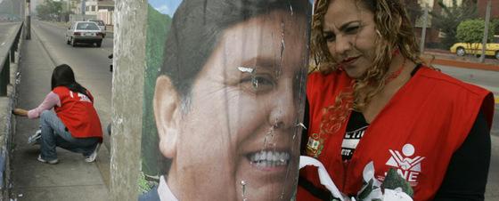 Una mujer retira un cartel de Alan García