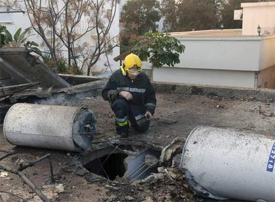 Un bombero observa el daño causado por un cohete sobre una vivienda de Naharía, al norte de Israel.- AP