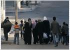 Residentes palestinos de la ciudad de Gaza caminan por una calle huyendo de los tanques israelíes.- AFP