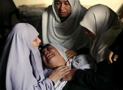 Mujeres palestinas lloran tras encontrar el cadáver de un familiar entre los restos de su casa en Beit Lahia, al norte de Gaza.- AP