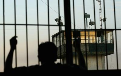 Un preso observa desde la ventana de su celda una torre de vigilancia en una cárcel mexicana.
