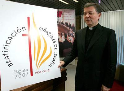 Juan Antonio Martínez Camino posa junto a un cartel que anuncia la beatificación de 498