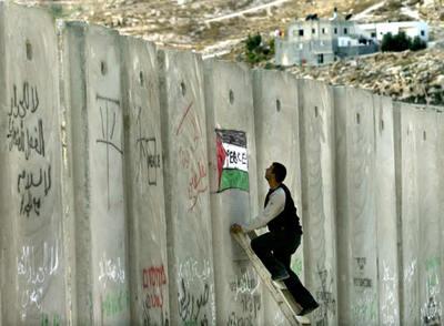 Un palestino pinta una bandera de Palestina en el muro de separación
