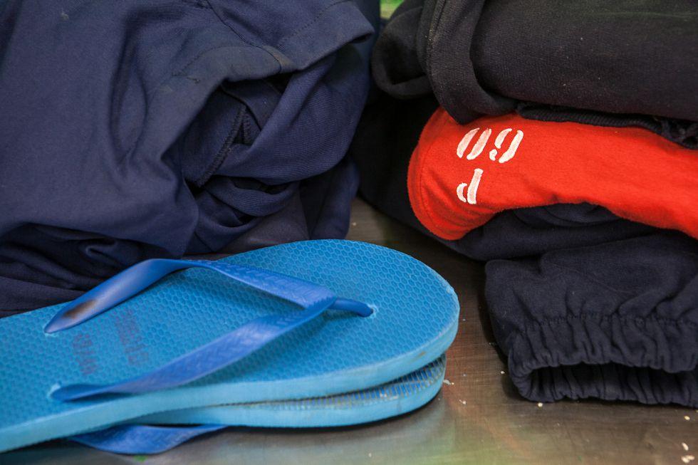 Os uniformes são marcados individualmente com um código. Os chinelos são uma maneira de evitar que sejam escondidos itens proibidos dentro dos sapatos.