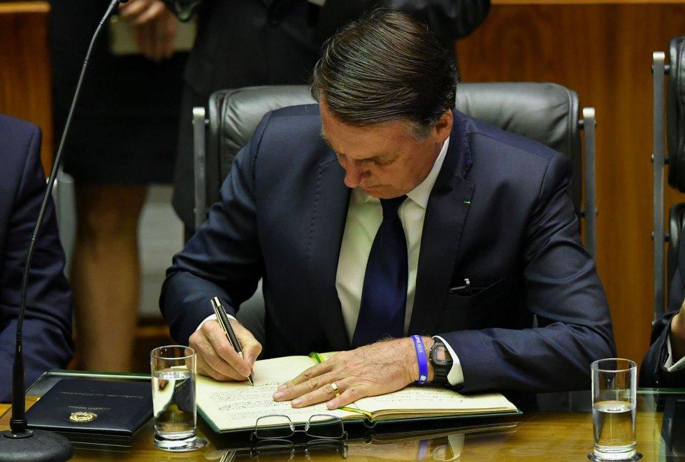 Jair Bolsonaro assina documento antes de fazer o juramento como presidente do Brasil.