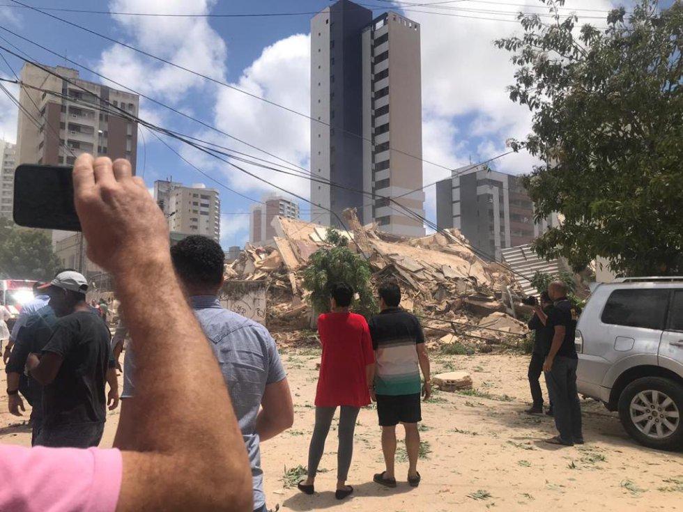 Pessoas observam os escombros de edifício residencial que desabou nesta terça-feira em Fortaleza.