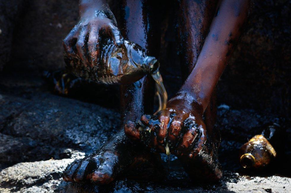 Garoto tenta retirar o petróleo do corpo, após atuar na remoção das manchas, no mar na Praia de Itapuama, Cabo de Santo Agostinho, Pernambuco.