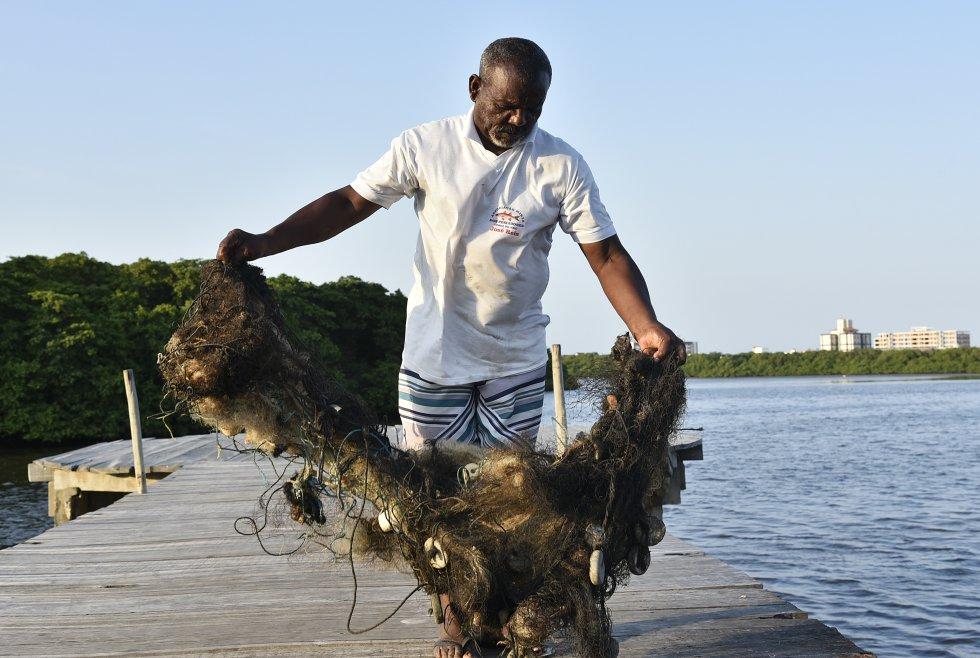 No manguezal da Coroa do Meio, em Aracaju, Sergipe, um pescador recolhe a rede encharcada pelo óleo.