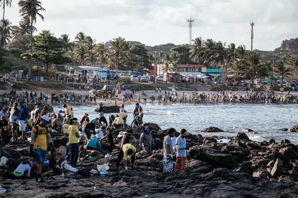 Uma multidão de voluntários se esforça para retirar o óleo da praia de Itapoama, em Cabo de Santo Agostinho, Pernambuco.