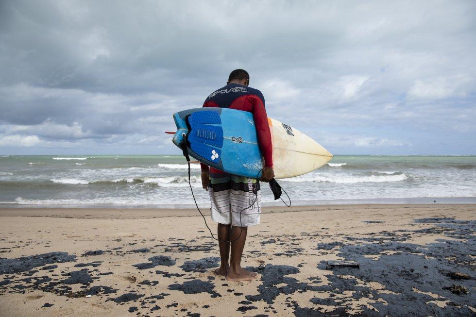 """O surfista Edson """"Parafina"""" observa desolado a condição da praia contaminada pelo óleo. Acostumados a surfar nas praias da região norte de Alagoas, os esportistas estão impossibilitados de entrar no mar devido ao vazamento."""
