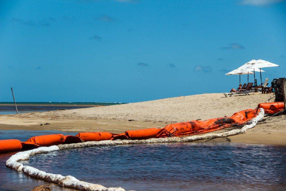 Uma turista toma sol ao lado da foz do rio Persinunga, que delimita a fronteira (na região litorânea) entre os estados de Pernambuco e Alagoas. A boia de contenção tenta evitar que o óleo se espalhe do mar em direção ao rio.