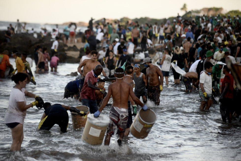 Na Pedra de Xaréu, Cabo de Santo Agostinho, Pernambuco, uma multidão de voluntários se organiza como pode para retirar o óleo da praia.
