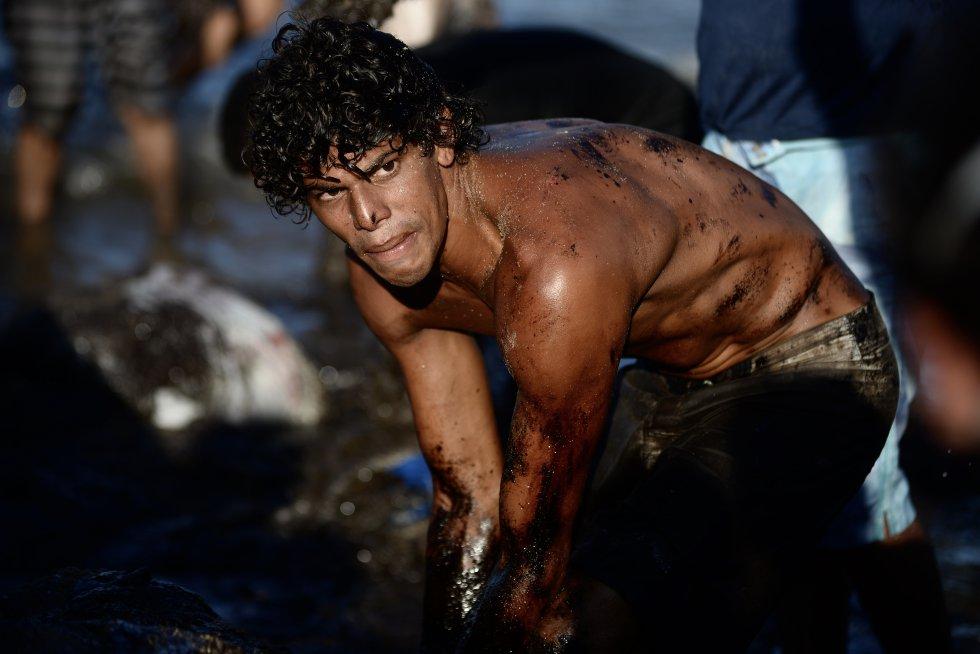 Um voluntário submerge as mãos na água do mar para retirar o óleo que contamina a praia de um dos maiores centros de turismo do Nordeste. Pedra de Xaréu, Cabo de Santo Agostinho, Pernambuco.