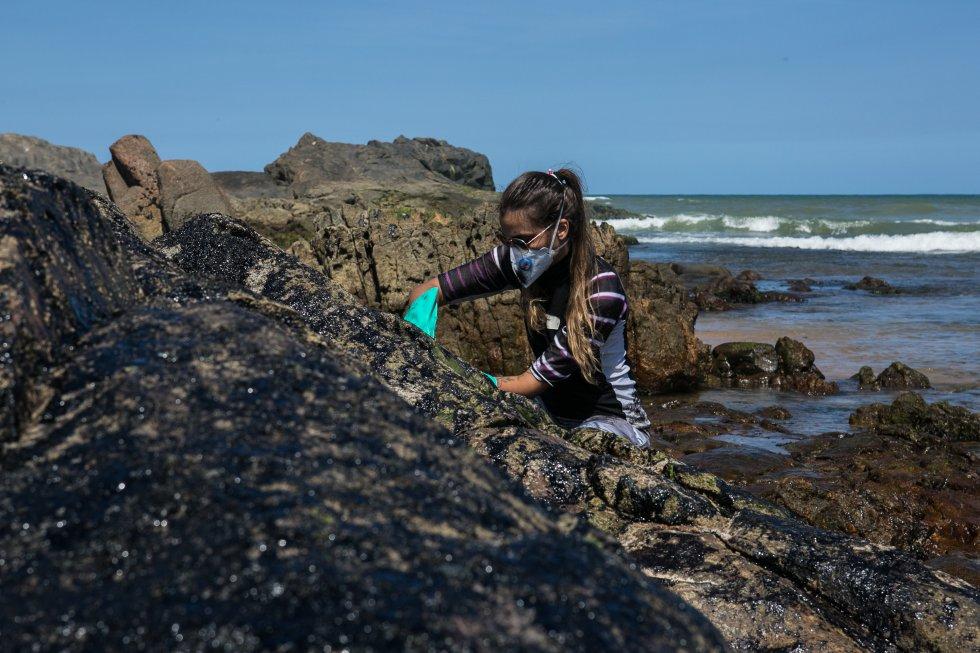 Luana, uma voluntária moradora da região, ajuda a limpar as pedras na famosa praia da Pedra do Sal, no bairro de Itapuã em Salvador, Bahia.