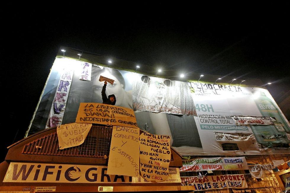 El cartel publicitario que cubre uno de los edificios de la Puerta del Sol se va cubriendo poco a poco con pancartas con eslóganes reivindicativos del Movimiento 15-M.