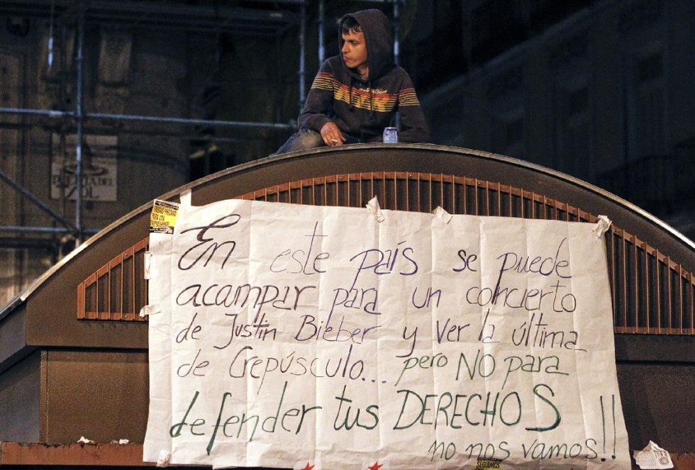 Los manifestantes no se van de la Puerta del Sol y se quejan, como dicen en esta pancarta que han colocado en un quiosco, que se pueda acampar en la calle para coger entradas para un concierto o ver una pelicula y no para defender los derechos de los ciudadanos.