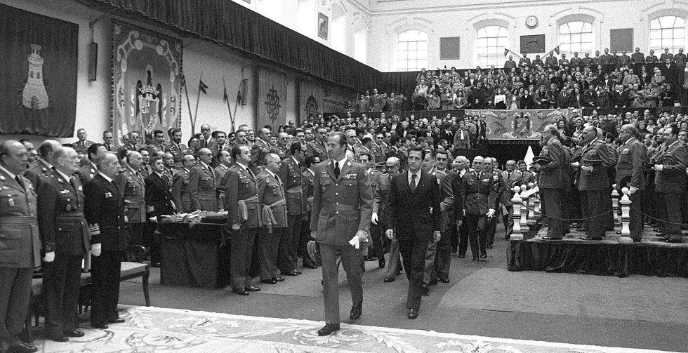 El rey Juan Carlos y el presidente del Gobierno, Adolfo Suárez, avanzan entre militares en pie en el acto de entrega de fajines de la 76º promoción de la Escuela de Estado Mayor. El acto se celebró el 27 de febrero de 1980.