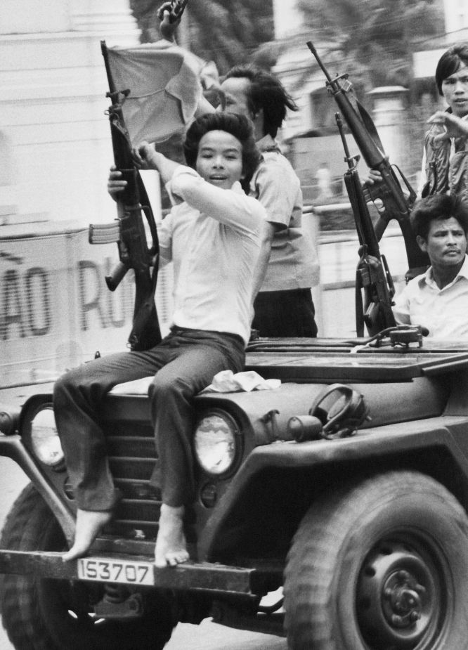 Un joven porta un arma y ondea la bandera del Gobierno Revolucionario Provisional por las calles de Saigón, 4 de mayo de 1975.
