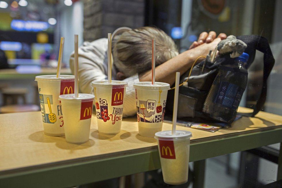 A morte de uma mulher que dormia em um McDonald´s em Hong Kong em outubro chamou a atenção para as pessoas sem lar que passam a noite nos estabelecimentos de comida rápida que permanecem abertos 24 horas por dia. O corpo da mulher sem vida esteve durante várias horas sobre a mesa sem que os clientes notassem que estava morta. Na imagem, um homem com seus pertences em um McDonald´s 24 horas em Hong Kong.