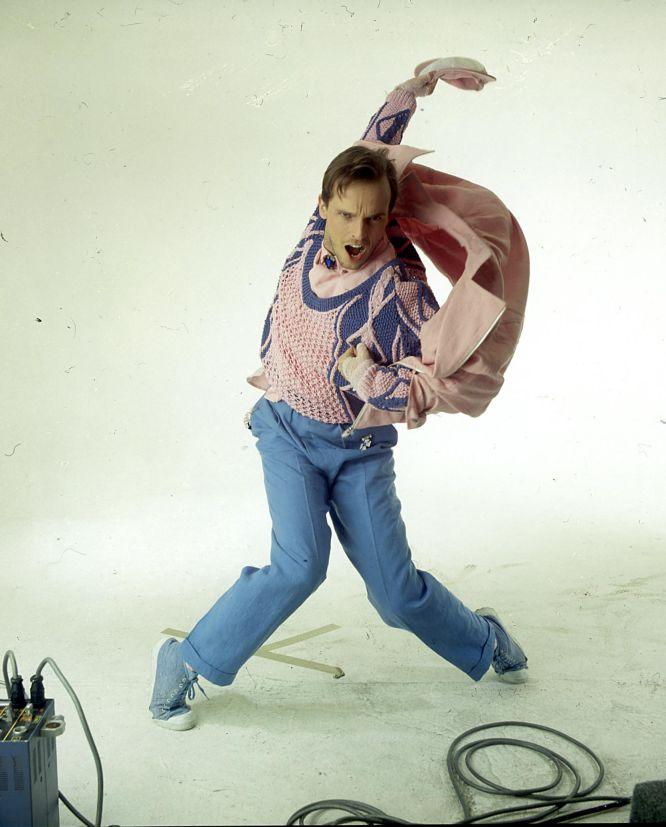 """Miguel Bosé quiso reinventar la estética masculina del momento. Durante mucho tiempo, los grises desaparecieron en sus estilismos y el color y las prendas extravagantes cobraron todo el protagonismo. Apostó por un look andrógino y parecía casi tan camaleónico como David Bowie. """"Hay tres cosas que los hombres hemos perdido y de las que os habéis apropiado las mujeres: las joyas, que se han llevado en todas las civilizaciones y que yo uso mucho, el maquillaje y la falda, ambos usados históricamente por el hombre"""", explicaba en una entrevista a 'Vanity Fair'. En la imagen, el cantante viste de Francis Montesinos en 1985."""