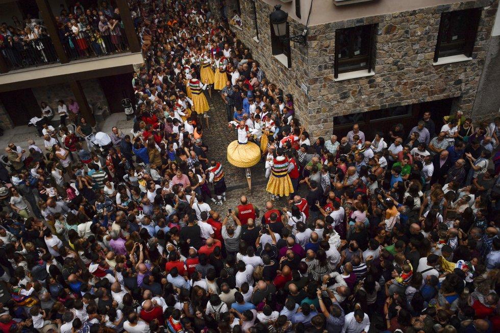 Miles de personas contemplan la bajada de los danzadores por una de las cuestas de Anguiano, La Rioja.