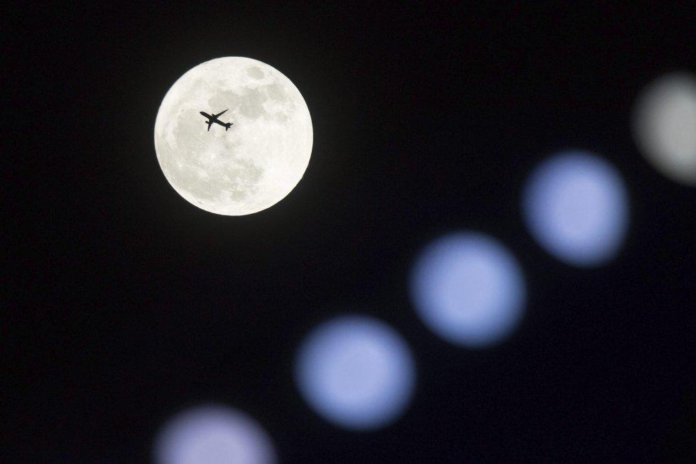 Un avión vuela frente a la Superluna en Hong Kong (China).