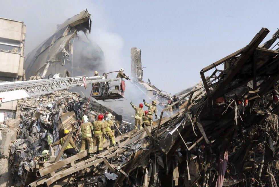 Miembros de los servicios de rescate iraníes buscan posibles víctimas entre los escombros del edificio Plasco.