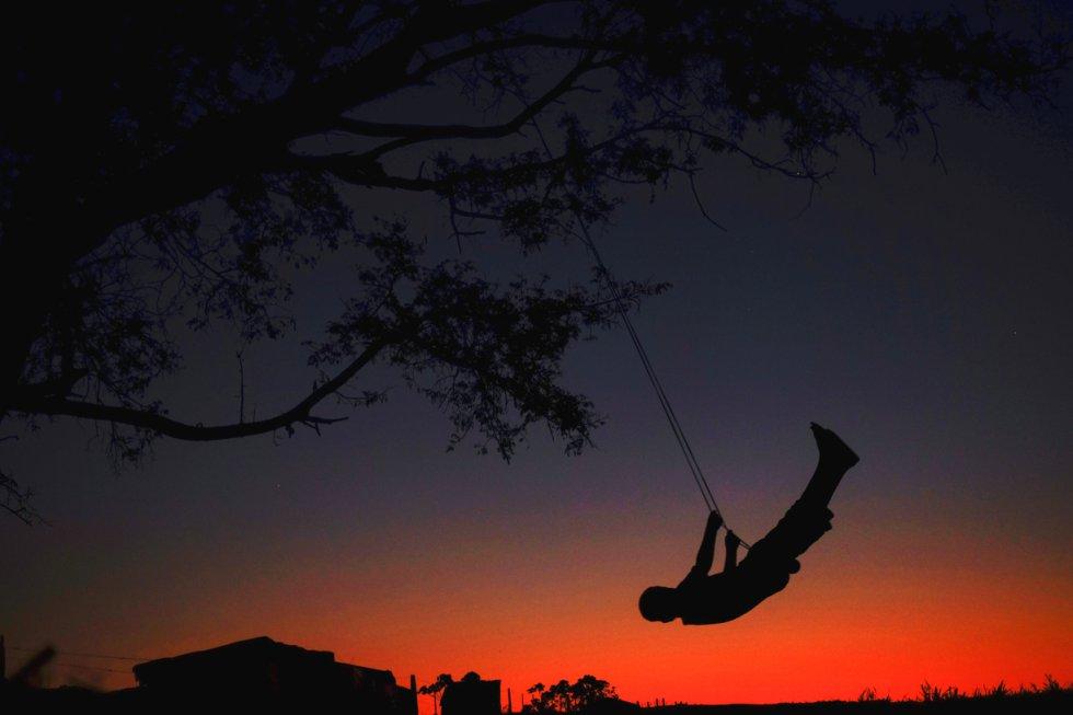 Afectados por la pérdida de sus terrenos a lo largo del último siglo, los guaraníes sufren una oleada de suicidios sin precedentes. Se calcula que casi 1.000 mujeres, hombres y niños guaraníes se han quitado la vida en los últimos 20 años. La lucha ha dejado sin infancia a los más pequeños. De los guaraníes que se han suicidado el más joven tenía nueve años. En la foto, un niño se columpia de un árbol ubicado cerca de una carretera.