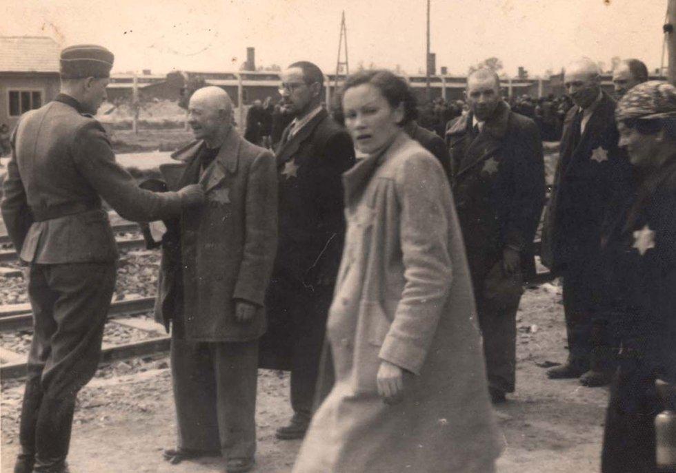 Un medico de las SS 'examina' el estado de salud de un judío. La mujer en primer plano se llama Geza Lajtos, de Budapest. Supervivientes del Holocausto pudieron reconocer a familiares en estas imágenes. De aquellos que era destinados a morir inmediatamente, fue en algunos casos el único recuerdo que quedó. El Álbum está incompleto porque Lilly Jacob-Zelmanovic Meier entregó fotos a los familiares que las pidieron.