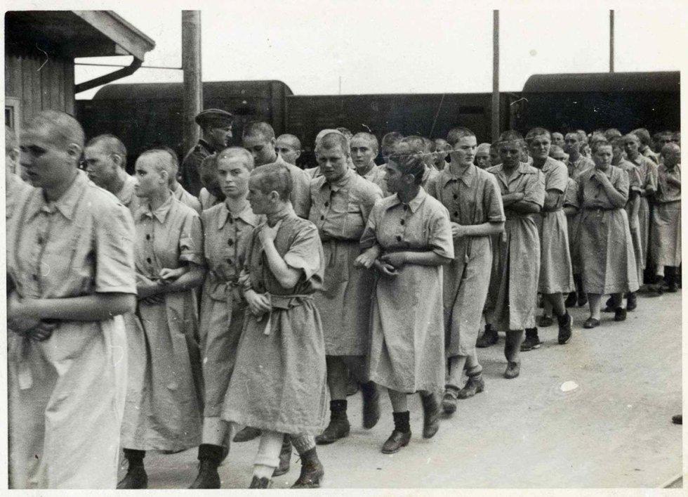 Prisioneras entran dentro del campo de mujeres, ya con el uniforme de prisioneros bajo la mirada de un guardia SS.