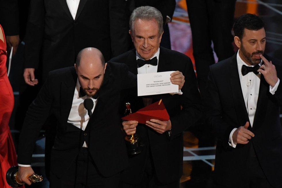 El actor Warren Beatty (centro) muestra el sobre correcto tras rectificar el error.
