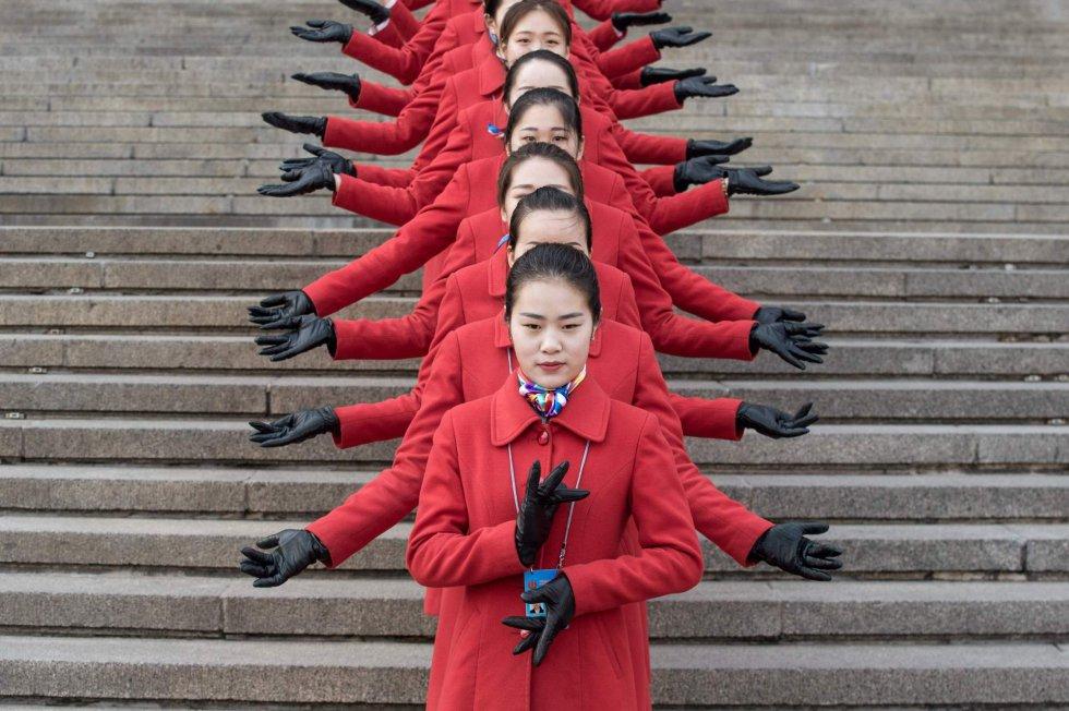 Azafatas posan durante la sesión de apertura de la Conferencia Consultiva Política del Pueblo Chino (CCPPCh) en el Gran Salón del Pueblo de Pekín.