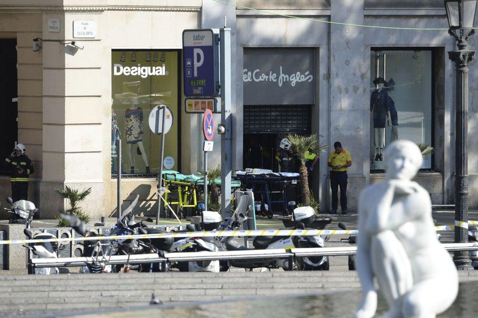 Policiais e membros do serviços de saúde permanecem junto a um shopping.