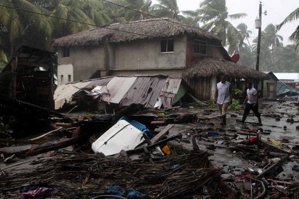 Unos hombres caminan junto a una vivienda destruida por el huracán en Nagua (República Dominicana), el 7 de septiembre.