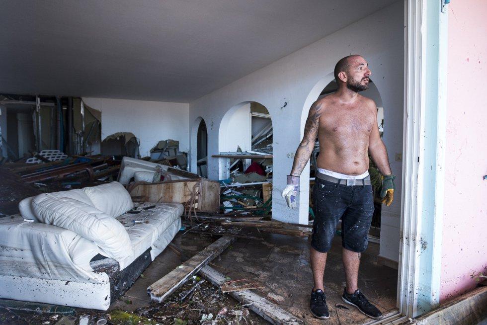 Un hombre limpia su vivienda destruida por los efectos del huracán en la bahía de Orient de la Isla de septiembre.