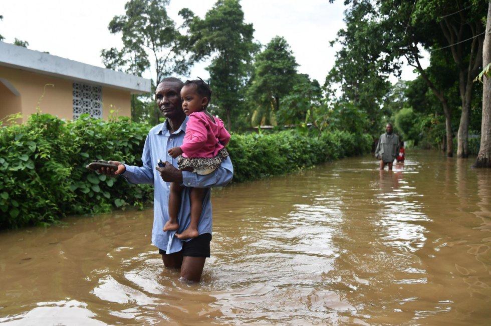 Un hombre camina con una niña en sus brazos por una calle inundada en Malfeti (Haití), el 8 de septiembre.