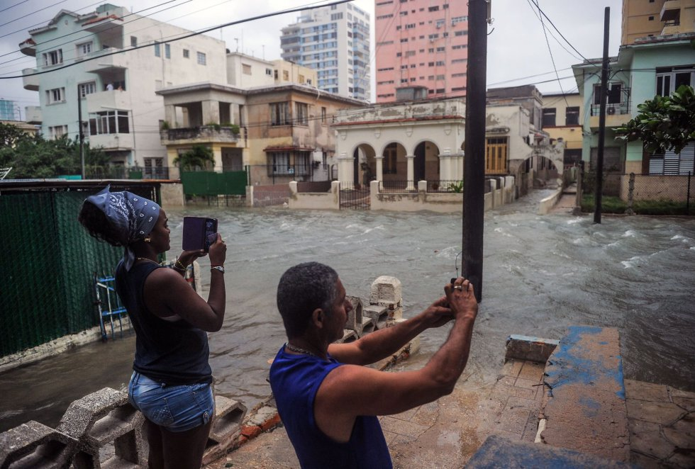 Una pareja toma fotografías de las calles anegadas de agua en La Habana.