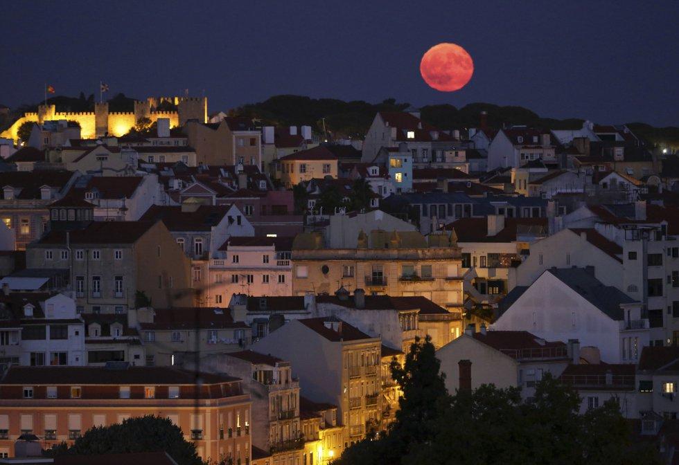 Vista de la luna llena tras el castillo de San Jorge en Lisboa (Portugal).