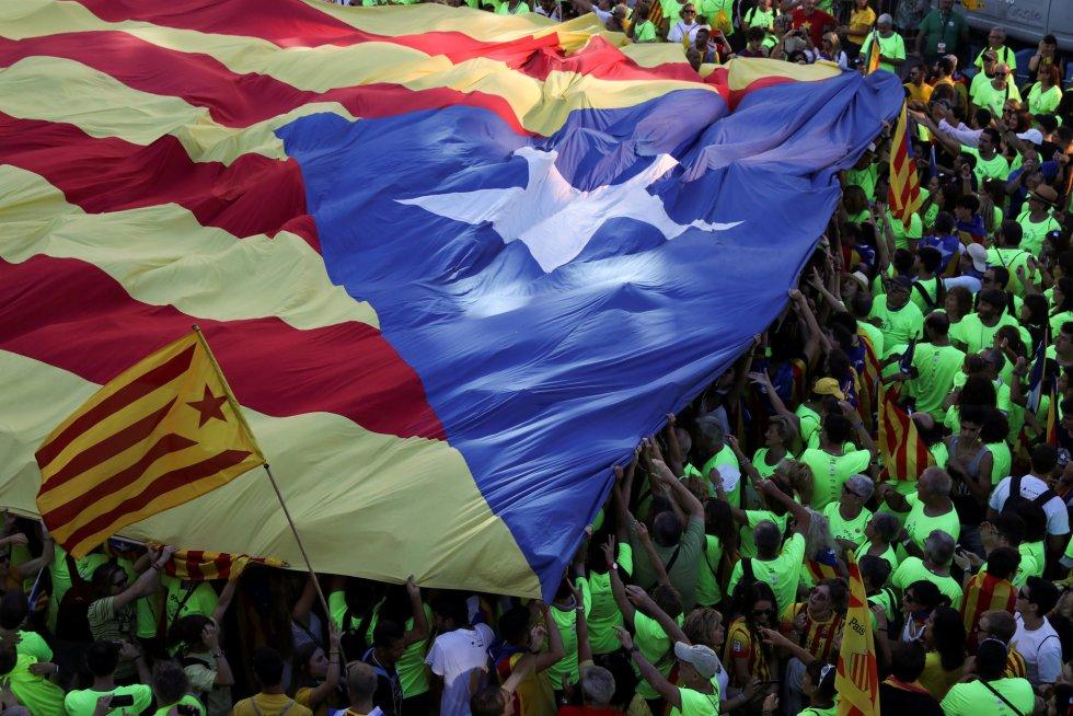 Una enorme bandera estelada es llevada por cientos de manifestantes.