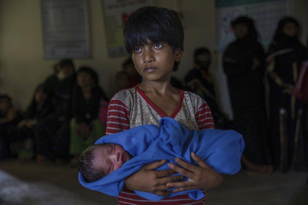 """Un portavoz del Gobierno birmano precisó que al menos 176 de los 471 pueblos habitados por los rohingya en el oeste de la mayoritariamente budista Birmania están vacíos después de que """"todo el pueblo huyera"""". En la imagen, una niña rohingya sujeta en brazos a su hermano recién nacido, en el campo de refugiados de Kutupalong (Bangladés)."""