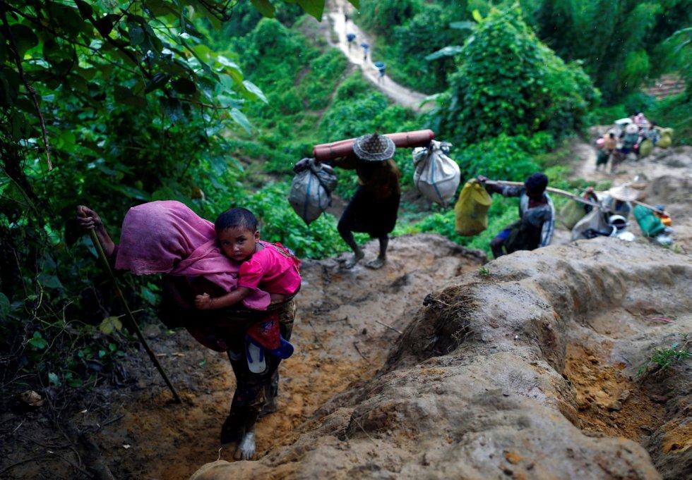 En la imagen, varios refugiados rohingya suben una colina, en Cox's Bazar, tras cruzar la frontera entre Myanmar y Bangladés.