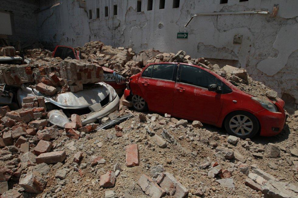 Vários carros ficaram soterrados entre os restos de um edifício derrubado pelo terremoto.