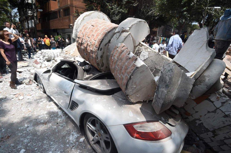Um carro ficou totalmente destruído depois ser atingido por escombros de prédios que caíram.