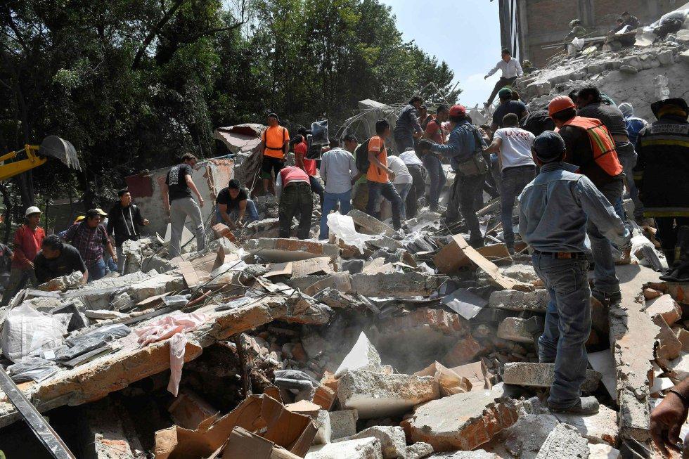 Ciudadanos y miembros de los servicios de emergencia retiran escombros en busca de víctimas tras el derrumbe de un edificio en Ciudad de México