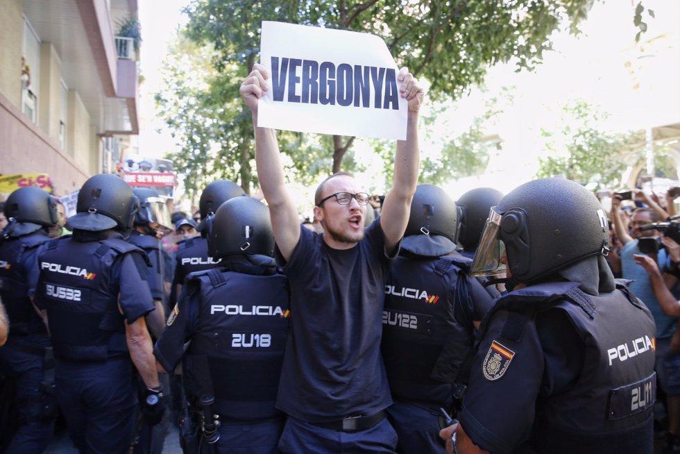 """Un manifestante alza un cartel en el que se puede leer """"Vergüenza"""" ante los antidisturbios."""