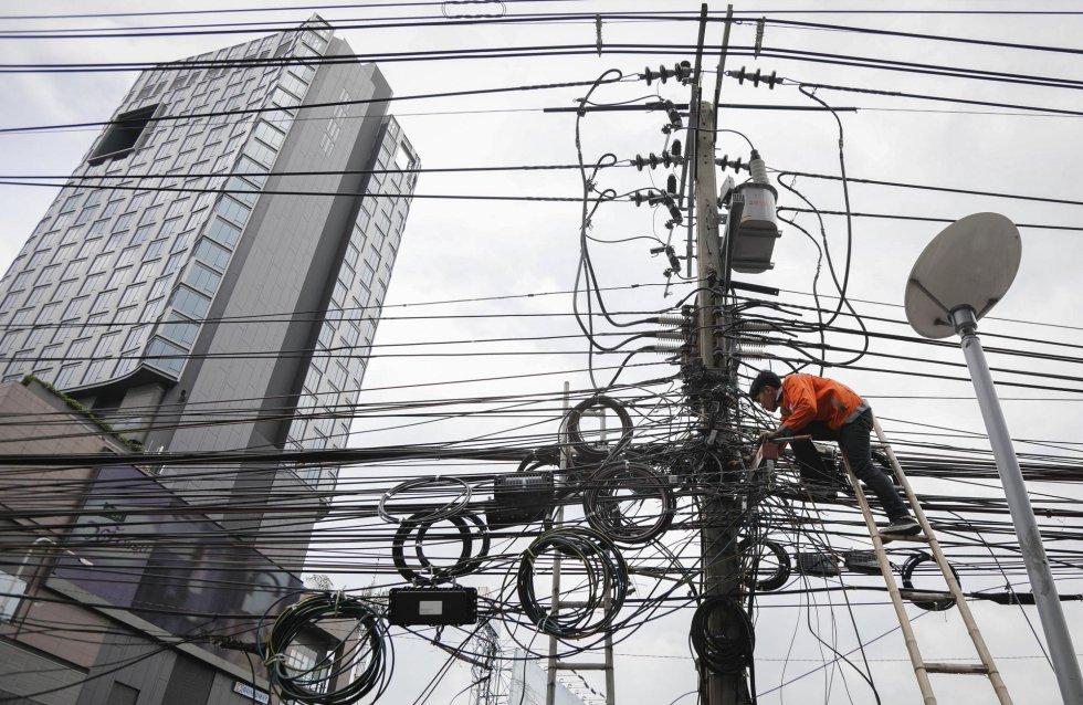 Un trabajador retira algunos cables de electricidad de una calle de Bangkok (Tailandia). El gobierno tailandés aprobó en 2016 un presupuesto para hacer subterráneos los cables de electricidad de la ciudad de Bangkok, con la intención de prevenir accidentes y mejorar la aparicencia de la ciudad.