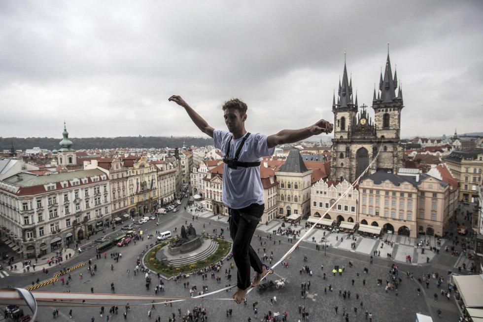 Un funambulista hace equilibrios sobre una cuerda floja en la Plaza de la Ciudad Vieja de Praga (República Checa).