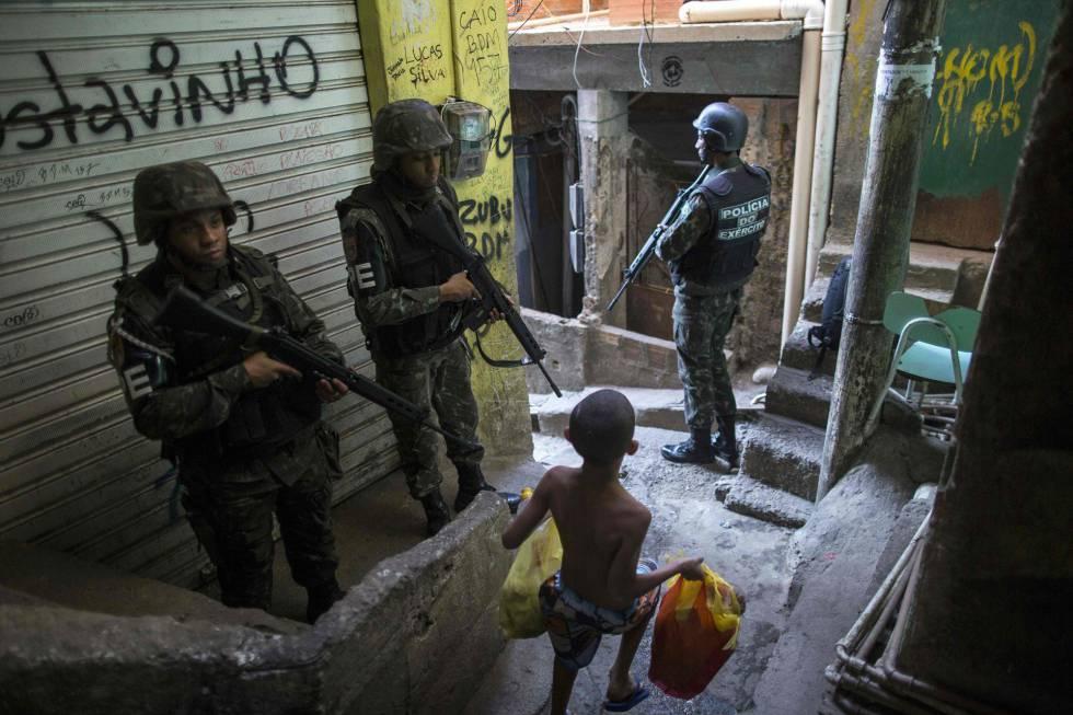 La policía militar del ejército brasileño patrulla a lo largo de un callejón en la favela de Rocinha, en Río de Janeiro (Brasil). Funcionarios de seguridad aseguran que la favela Rocinha vuelve a estar bajo control después de que cientos de soldados y policías fueran enviados a combatir traficantes de drogas armados.
