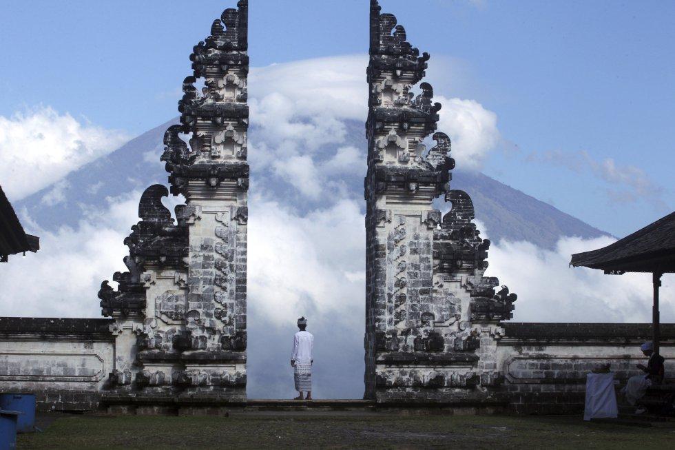 Un hombre observa el volcán Agung, cubierto de nubes, desde un templo de Karangasem (Indonesia).